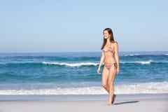 вдоль детенышей женщины пляжа песочных гуляя Стоковое Изображение