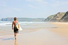 вдоль пляжа его гулять серфера surfboard Стоковые Фотографии RF