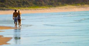 вдоль прогулки пар пляжа любящей Стоковые Изображения