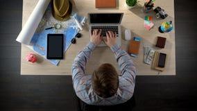Вебсайт человека посещая бюро путешествий для того чтобы увидеть предложенные путешествия, планируя каникулы стоковое фото rf