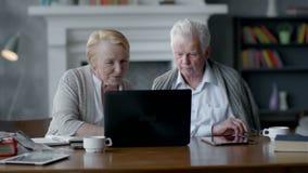 Веб-камера, пожилая пара имея потеху в связывать с семьей на интернете в удобной живущей комнате акции видеоматериалы