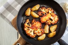 Вегетарианец зажарил в духовке стейк цветной капусты с картошками зажаренными herbsand Стоковое Фото