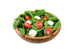 Вегетарианская еда и здоровая концепция образа жизни - салат весны с томатом вишни, сыром моццареллы и arugula в деревянном шаре Стоковые Фотографии RF
