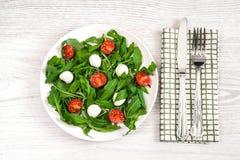 Вегетарианская еда и здоровая концепция образа жизни - салат весны с томатом вишни, сыром моццареллы и arugula на белом Ла плиты Стоковая Фотография RF