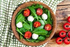 Вегетарианская еда и здоровая концепция - салат весны с томатом вишни, сыром моццареллы и arugula на шаре wodden Стоковые Фото