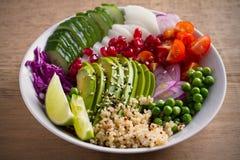 Вегетарианская здоровая еда: квиноа, авокадо, гранатовое дерево, томаты, зеленые горохи, редиска, красная капуста и салат известк Стоковые Фотографии RF