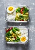 Вегетарианская коробка для завтрака - потушенные овощи, рис и вареное яйцо на серой предпосылке, взгляд сверху белизна студии мак стоковая фотография rf