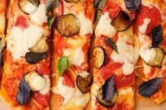 Вегетарианская пицца с aubergines и листьями базилика отрезала в нашивках Стоковая Фотография RF