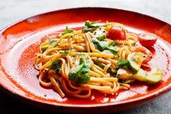 Вегетарианские макаронные изделия с томатами, avacado и сквошом Серая предпосылка, взгляд сверху, конец вверх стоковые фото