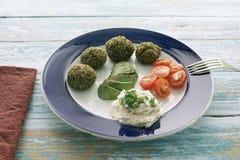 Вегетарианские фрикадельки горохов, шпината, базилика, квиноа, овсов и яйца на винтажной голубой древесине сопровоженной томатом  стоковые изображения rf