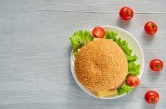 Вегетарианский бургер украшенный с свежими томатами вишни на серой конкретной предпосылке с космосом экземпляра Классический амер Стоковое Изображение