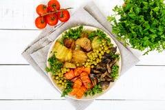 Вегетарианский завтрак: испеченные картошки овощей, моркови, грибы, зеленые горохи на плите на белой деревянной предпосылке Стоковое Фото