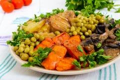 Вегетарианский завтрак: испеченные картошки овощей, моркови, грибы, зеленые горохи на плите на белой деревянной предпосылке Стоковые Фото