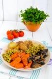 Вегетарианский завтрак: испеченные картошки овощей, моркови, грибы, зеленые горохи на плите на белой деревянной предпосылке Стоковое Изображение RF