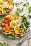 Вегетарианский салат при зеленые фасоли, зажаренный цукини, томаты, нуты, моркови и вареные яйца взбрызнутые с свежими травами в  Стоковые Фотографии RF