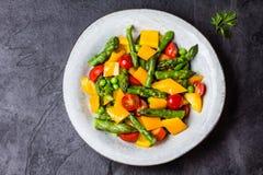 Вегетарианский салат с спаржей, томатами вишни, болгарским перцем, предпосылкой шифера Стоковое фото RF