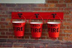 Ведра огня аварийные на кирпичной стене стоковые фотографии rf
