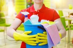 Ведро чистящих средств в руках уборщиков стоковое фото