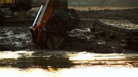 Ведро экскаватора выкапывает почву от дна реки на заходе солнца Очищающ и углубляющ канал сток-видео