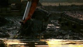 Ведро экскаватора выкапывает почву от дна реки на заходе солнца Очищающ и углубляющ канал акции видеоматериалы