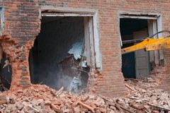 Ведро экскаватора ломает дом стоковое фото rf
