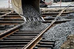 Ведро экскаватора льет гравий на рельсах трамвая во время работ ремонта и замены Дороги и городская экономика стоковое фото rf