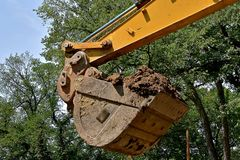 Ведро backhoe заполненного с грязью стоковая фотография
