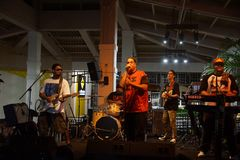 Ведущий певец декана Peni поя в mic как диапазон сжимает на этапе стоковые изображения rf