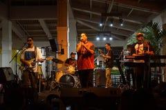 Ведущий певец декана Peni поя в mic как диапазон сжимает на этапе стоковое фото rf