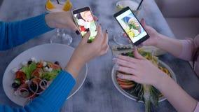 Ведущ блог, руки девушек наблюдая фото красивой еды на мобильном телефоне во время вкусного обеда диеты для потери веса видеоматериал
