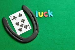 Везение слова показанное с играя карточкой 7 клеверов и подковы на день Patricks Святого стоковые фото
