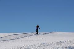 Вездеходный лыжник в зиме против голубого неба Стоковое Изображение RF