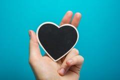 вектор знака сетки влюбленности Черное сердце доски в руках женщины на голубой предпосылке Стоковое Изображение