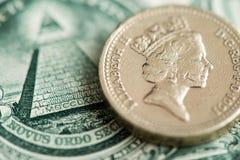 Великобританская стерлинговая монетка фунта и США банкноты одного доллара стоковое фото rf