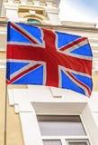 Великобританский флаг летает на здание старой гостиницы в туристском городе Стоковая Фотография