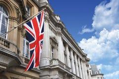 Великобританский флаг Юниона Джек на поляке с зданиями и красивым пасмурным голубым небом Стоковая Фотография RF