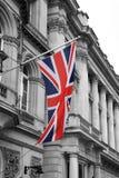 Великобританский флаг Юниона Джек на поляке с черно-белыми зданиями Стоковое фото RF