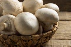 Величают champignons в плетеной корзине на деревянной предпосылке Стоковая Фотография