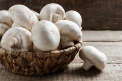Величают champignons в плетеной корзине на деревянной предпосылке Стоковые Фотографии RF