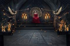Величественная женщина в красном luxuious платье сидя на троне в королевском интерьере стоковые фотографии rf