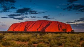 Величественное Uluru на заходе солнца на ясном вечере ` s зимы в северных территориях, Австралии Стоковые Фото