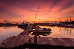 Величественный восход солнца при шлюпка отдыхая около дока как foregrou Стоковые Изображения RF
