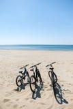 3 велосипеда на пляже на предпосылке моря Стоковое фото RF