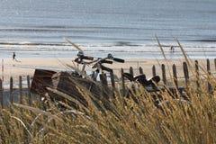 2 велосипеда полагаясь против деревянной загородки на пляже Стоковые Фото