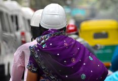 Велосипедисты велосипед нося шлемы безопасности захваченные от улиц города Индии Стоковое Фото