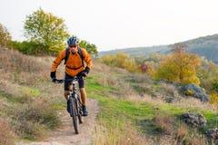 Велосипедист в апельсине ехать горный велосипед на следе осени скалистом Весьма спорт и концепция Enduro велосипед стоковое фото