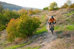 Велосипедист в апельсине ехать горный велосипед на следе осени скалистом Весьма спорт и концепция Enduro велосипед стоковые изображения rf