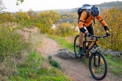 Велосипедист в апельсине ехать горный велосипед на следе осени скалистом Весьма спорт и концепция Enduro велосипед стоковая фотография rf
