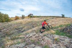 Велосипедист в красном цвете выбирая велосипед вверх на следе осени скалистом Весьма спорт и концепция Enduro велосипед Стоковая Фотография