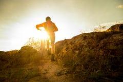 Велосипедист в красном цвете выбирая его горный велосипед на следе осени скалистом на заходе солнца Весьма спорт и концепция Endu Стоковое фото RF